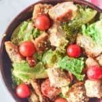 overhead view of chicken Caesar salad in a wood bowl