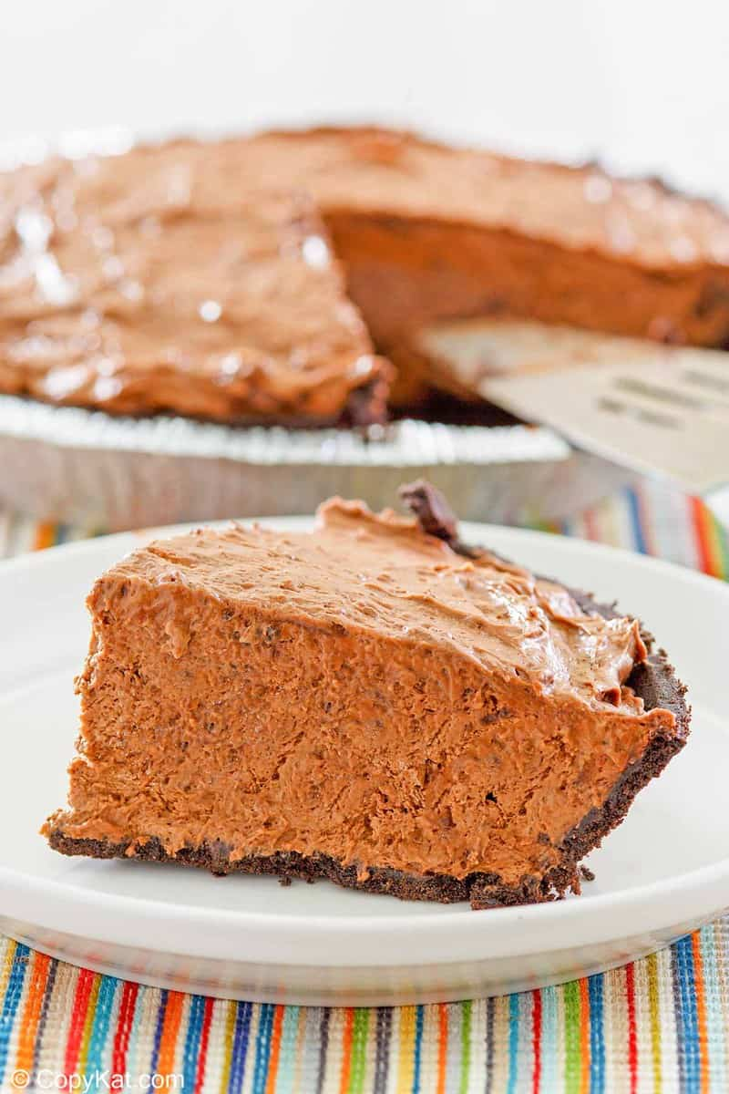 a slice of chocolate pudding pie on a plate in front of the pie