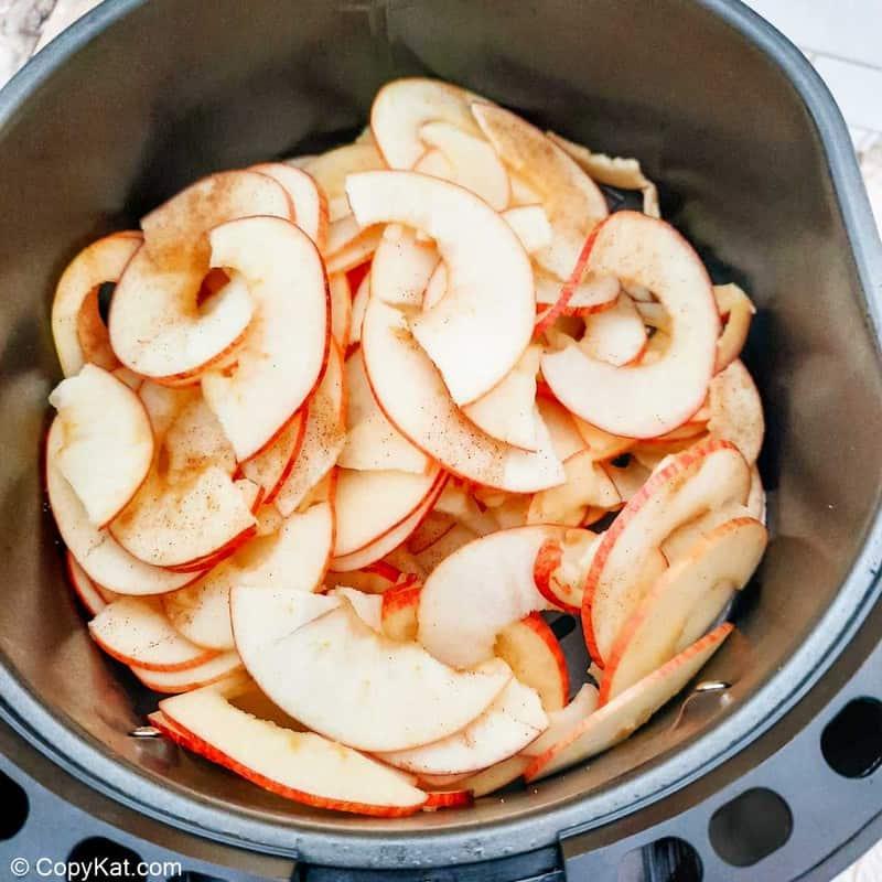 cinnamon sugar apple slices in an air fryer basket