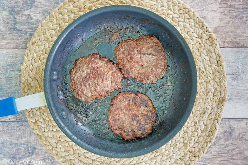three cooked hamburger patties in a skillet