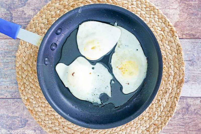 three fried eggs in a skillet