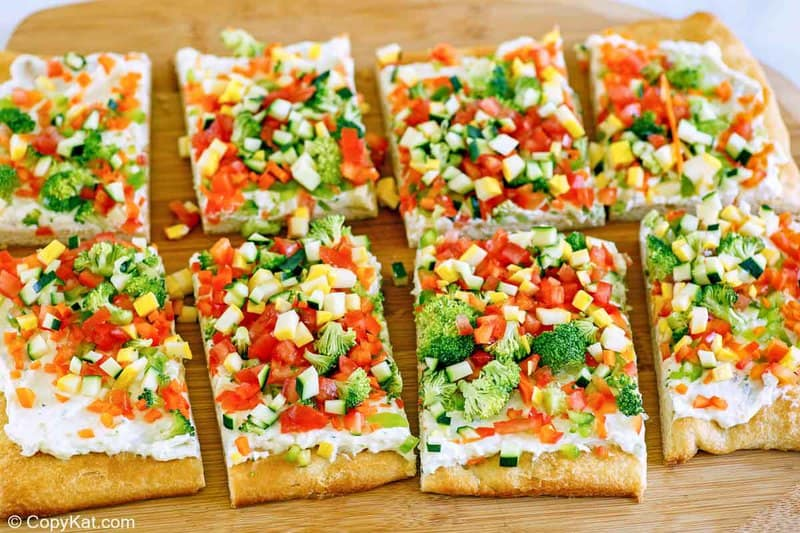 crescent roll veggie pizza slices on a cutting board