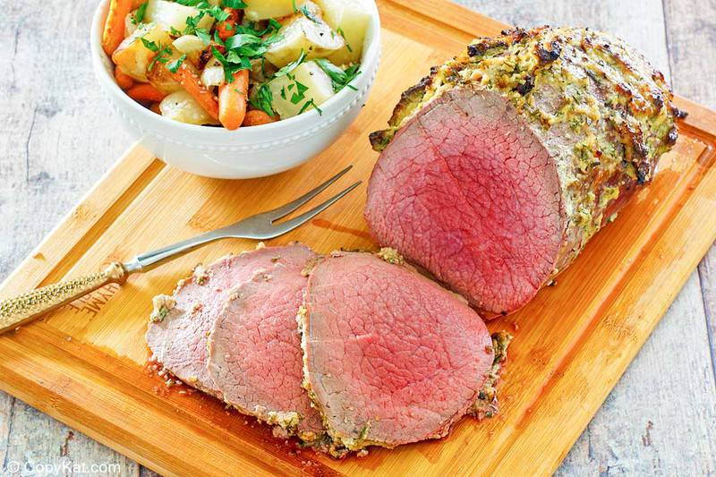eye of round roast, roast slices, bowl of vegetables, and meat fork on a cutting board