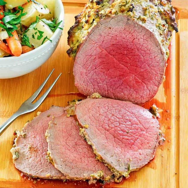 eye of round roast and a bowl of vegetables on a cutting board