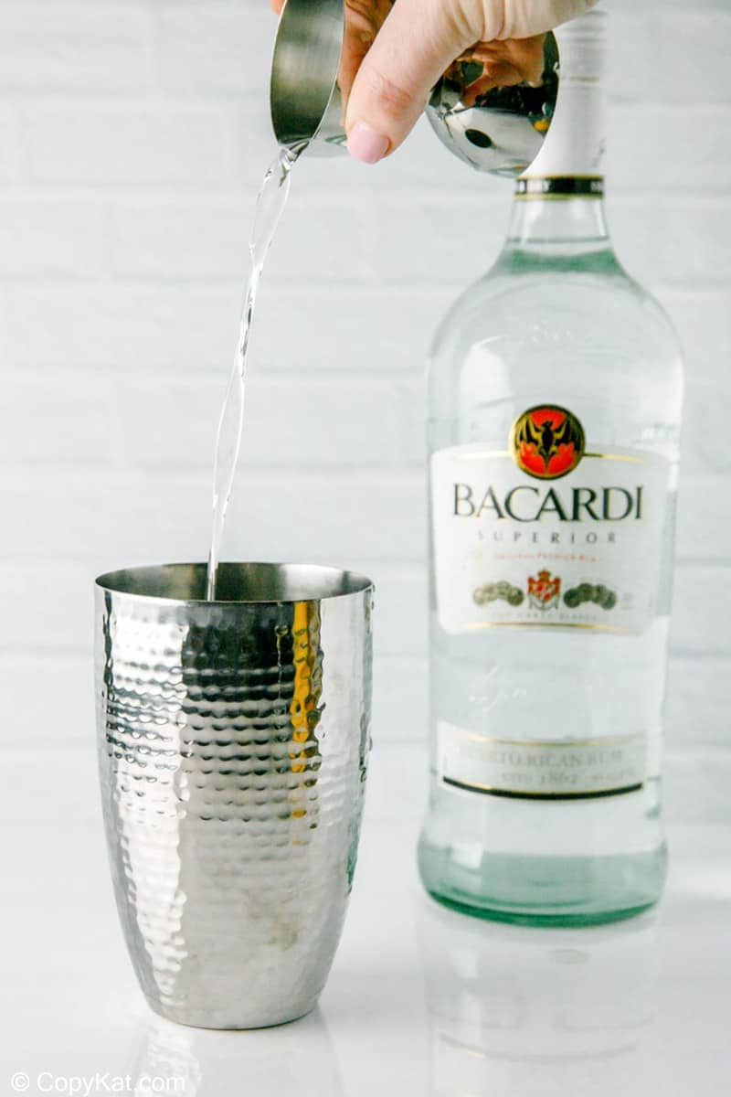 pouring Bacardi light rum into a cocktail shaker