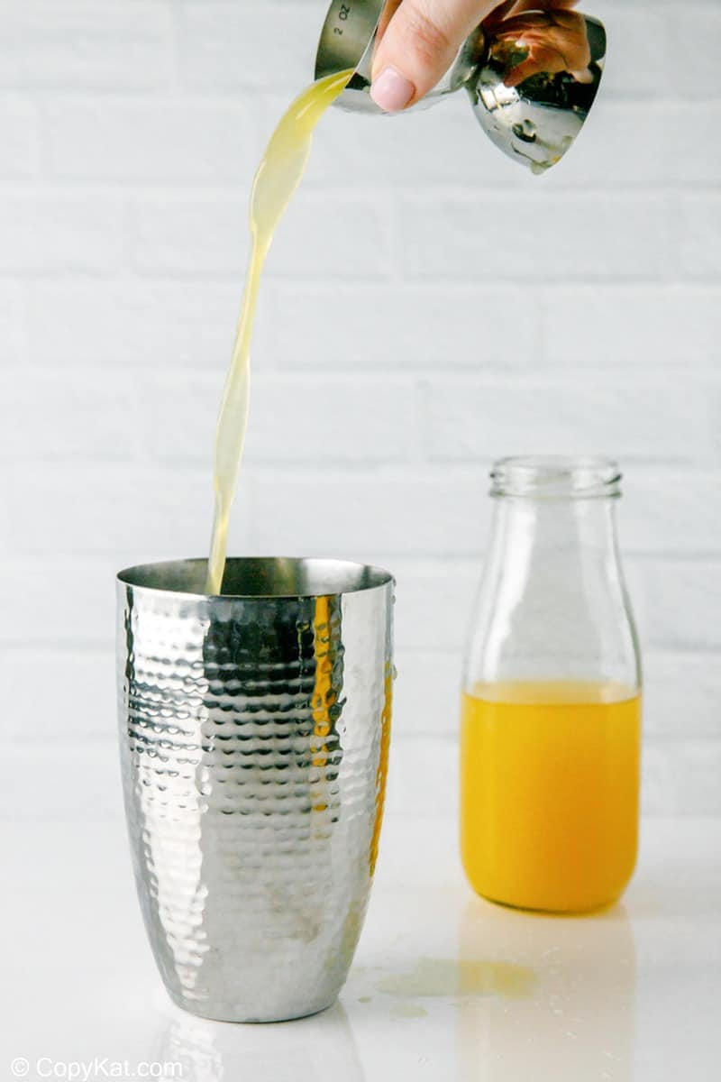 pouring orange curacao into a cocktail shaker