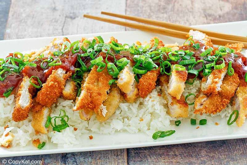 pork katsu with tonkatsu sauce over rice on a platter