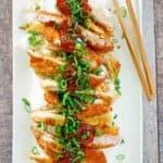 overhead view of pork katsu, tonkatsu sauce, rice, and chopsticks on a platter