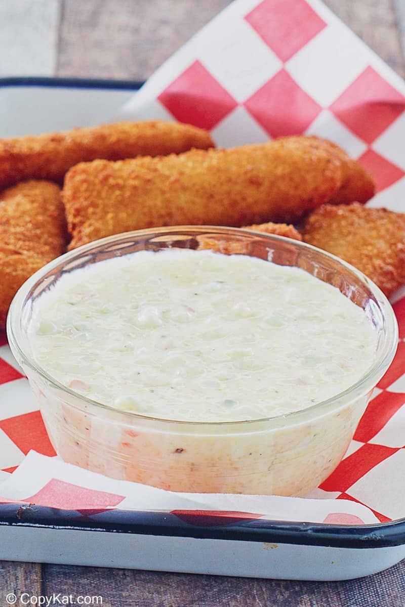 a bowl of homemade Red Lobster tartar sauce on a tray with fish sticks