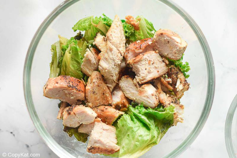 romaine lettuce and chicken pieces in a bowl