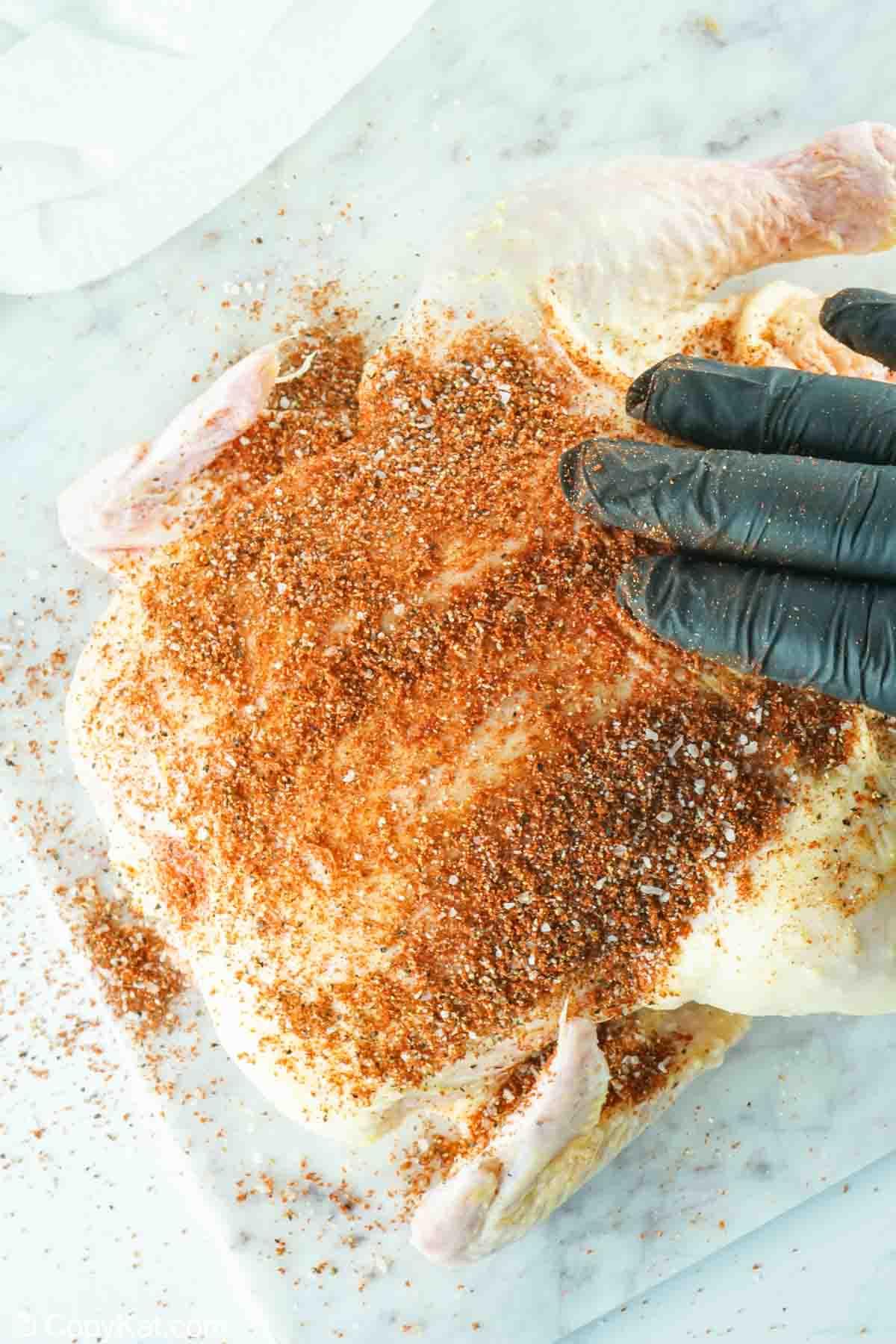 rubbing seasoning on a whole chicken