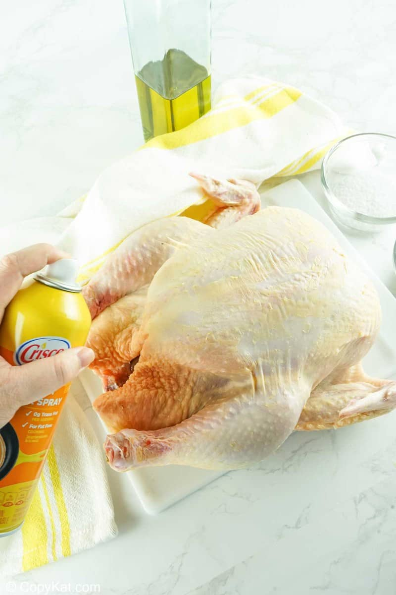 spraying butter cooking spray on a whole chicken
