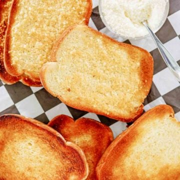overhead view of texas toast slices and a bowl of parmesan cheese