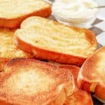 slices of texas toast and a bowl of parmesan cheese