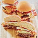 three breakfast burgers on a wood board