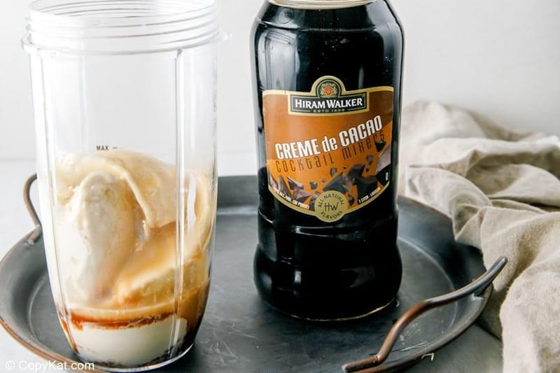 adding dark creme de cacao to a blender for a brandy alexander