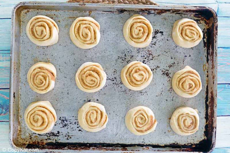 cinnamon roll dough slices on a baking sheet