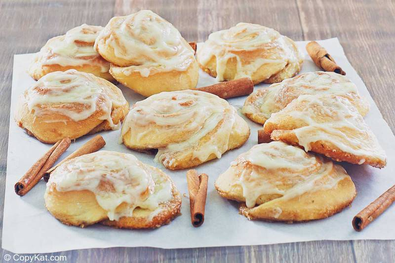 frosted cinnamon rolls and cinnamon sticks on parchment paper
