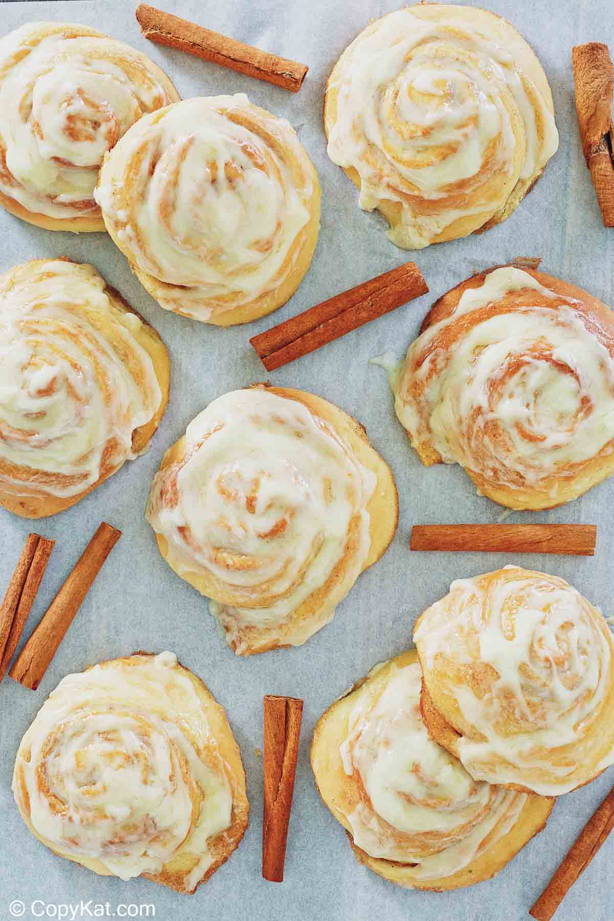 overhead view of frosted cinnamon rolls and cinnamon sticks