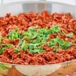 chili colorado con carne in a skillet topped with chopped cilantro