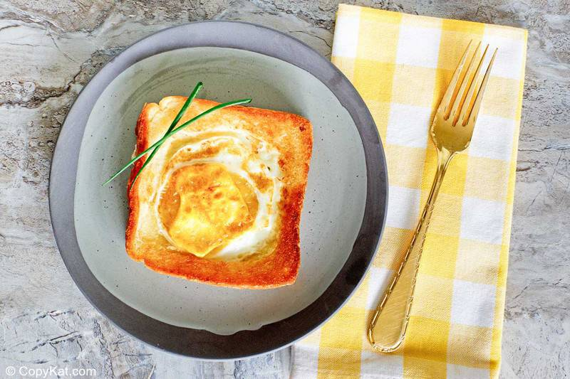 egg in a basket on a plate and a fork on a napkin