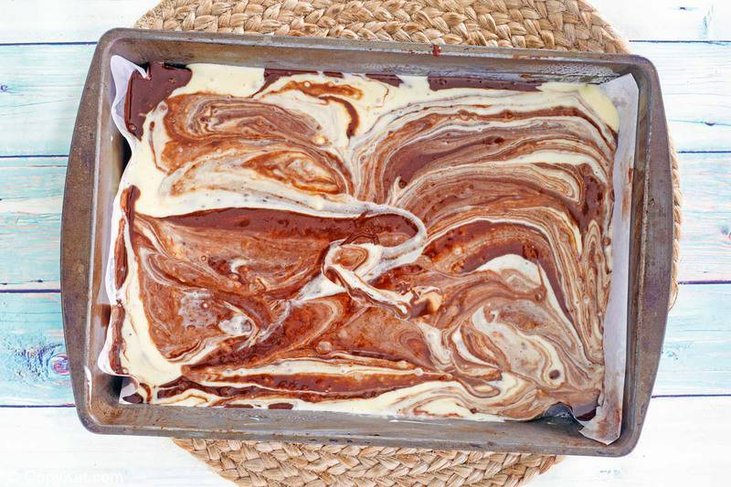 swirled chocolate and cream cheese brownie batter in a baking dish