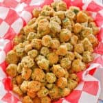 fried okra in a basket lined with parchment paper