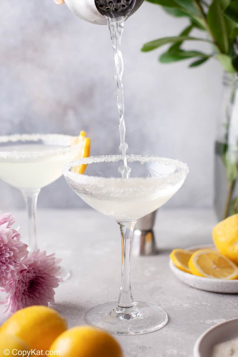 pouring a lemon drop martini into a sugar rimmed glass