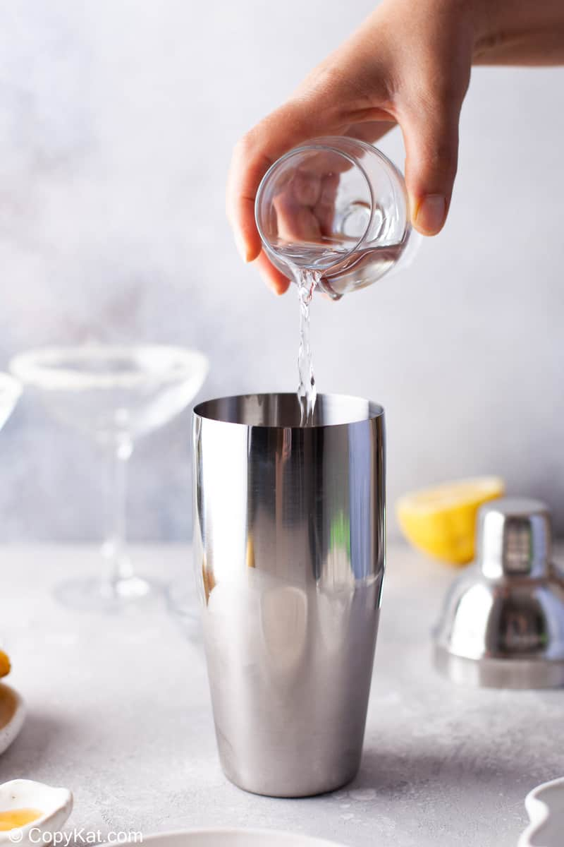 pouring vodka into a cocktail shaker