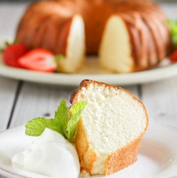 slice of Scandinavian almond cake on a plate in front of the cake