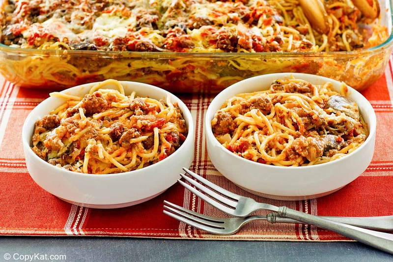 spaghetti casserole in two bowls and a baking dish