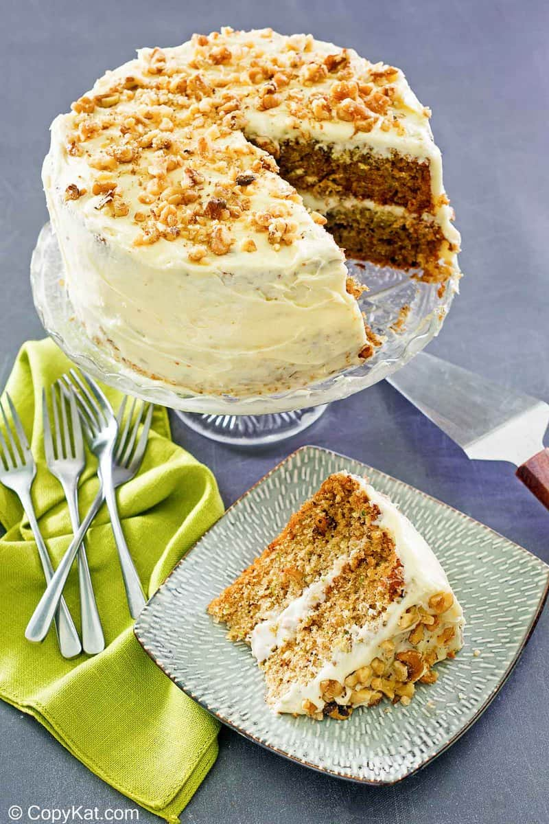 zucchini cake slice on a plate and the cake on a stand