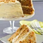 zucchini cake with cream cheese frosting on a cake stand and a slice on a plate