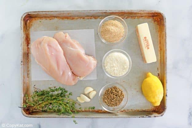lemon pepper chicken ingredients on a baking sheet.