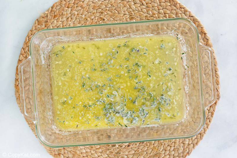 melted butter, garlic, thyme, and lemon juice in a baking dish.