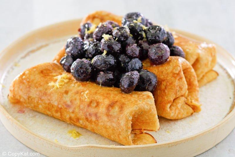 three cheese blintzes topped with blueberries and lemon zest on a plate.