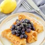three cheese blintz topped with blueberries on a plate, a lemon, knife, and fork.
