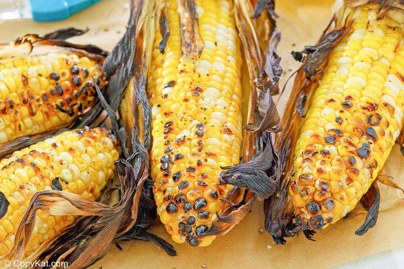 grilled corn on the cob with husks.