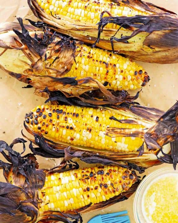 overhead view of grilled corn on the cob on parchment paper.