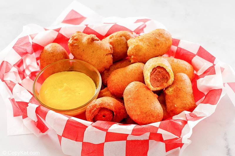 mini corn dogs and mustard in a serving basket.