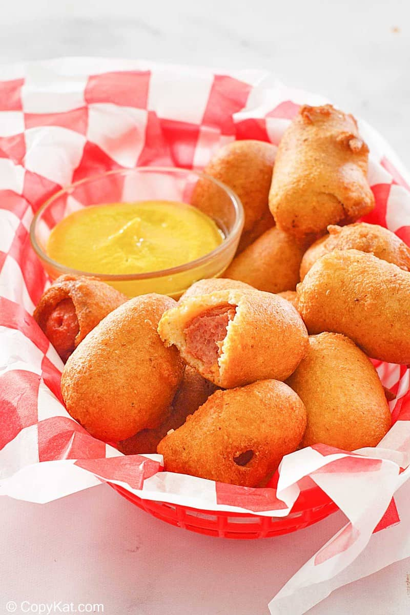 mini corn dogs and a small bowl of mustard in a basket.