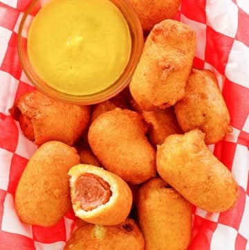 mini corn dogs and mustard on parchment paper.