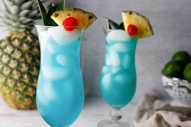 two homemade Olive Garden Blue Hawaiian drinks and a pineapple