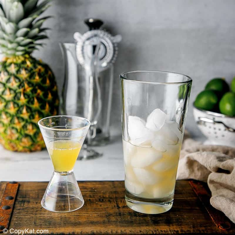 pineapple juice in a jigger next to a glass with ice and sour mix
