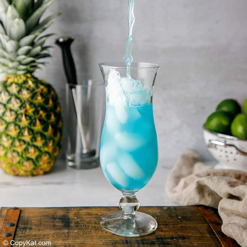 pouring a homemade Olive Garden Blue Hawaiian into a glass with ice