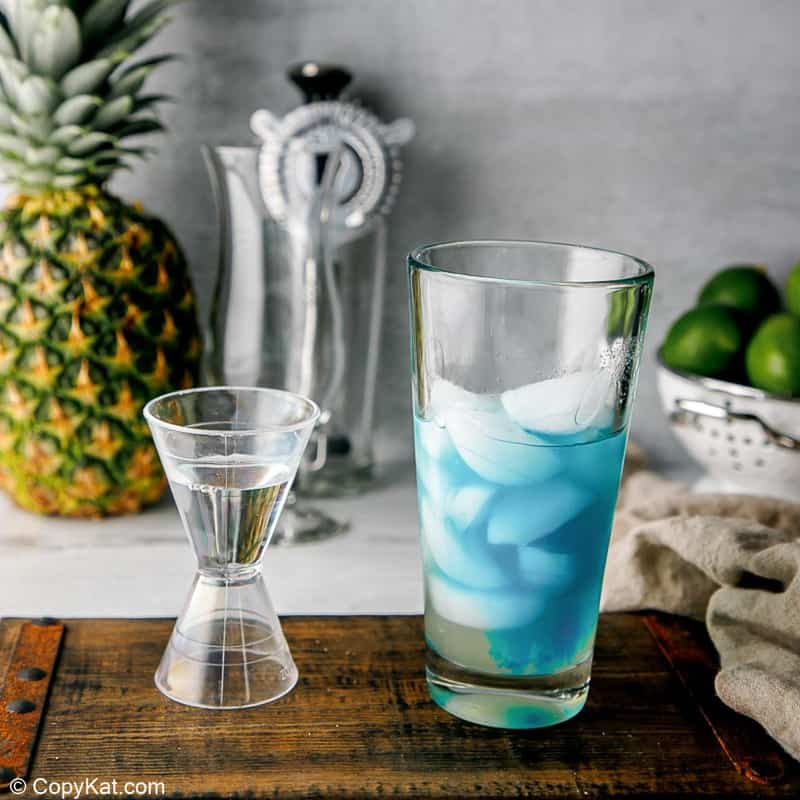 rum in a jigger next to a glass with ice, rum, and blue curacao