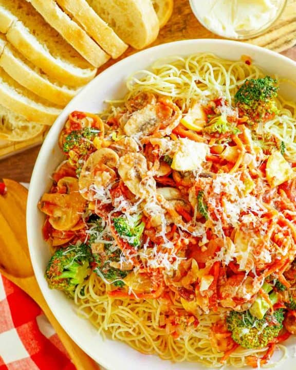 overhead view of homemade Olive Garden capellini primavera next to bread slices and butter