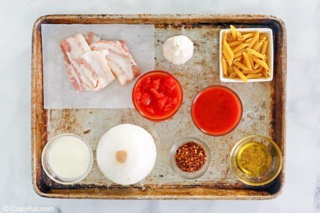 penne alla vodka ingredients on a baking sheet.