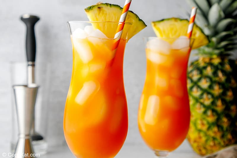 two glasses of spiced rum punch garnished with pineapple