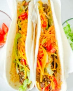 two homemade Taco Bell soft tacos with beef, lettuce, cheese, and tomatoes